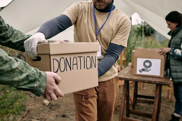 Jovem de luvas levando caixa com doação realizada por pessoa de uniforme