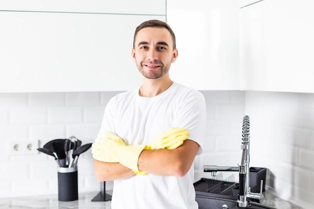 Jovem de luvas na cozinha em casa