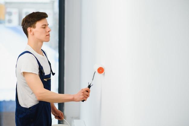 Jovem de macacão azul pintando a parede em branco com um rolo