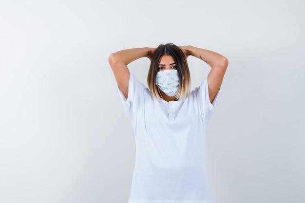 Jovem de mãos dadas atrás da cabeça em uma máscara e camiseta branca e parece confiante. vista frontal.