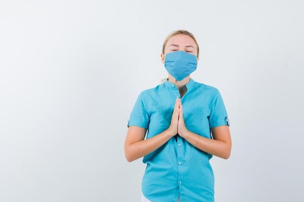 Jovem de mãos dadas em gesto de oração com camiseta, máscara e aparência esperançosa