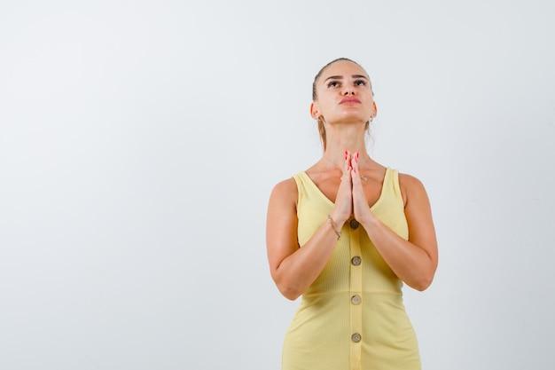 Jovem, de mãos dadas em gesto de oração em vestido amarelo e parecendo esperançoso. vista frontal.