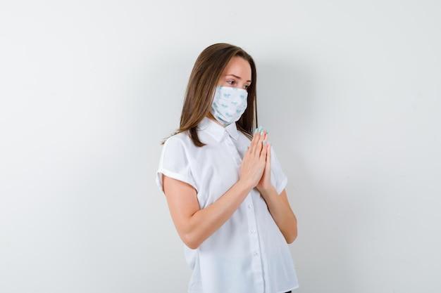Jovem de mãos dadas em gesto de oração