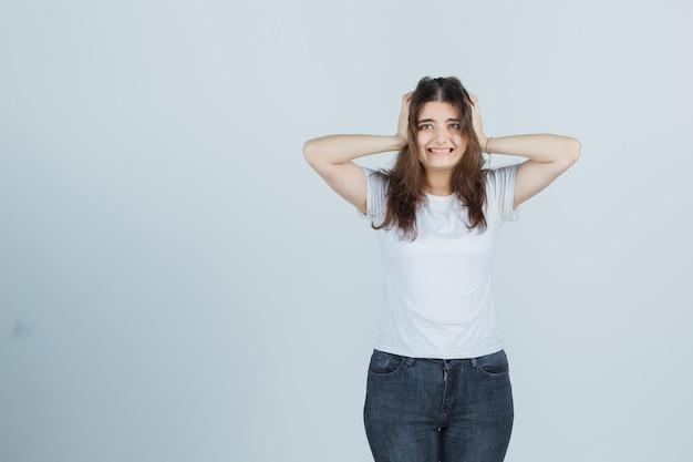 Jovem de mãos dadas na cabeça em t-shirt, jeans e parecendo confusa, vista frontal.