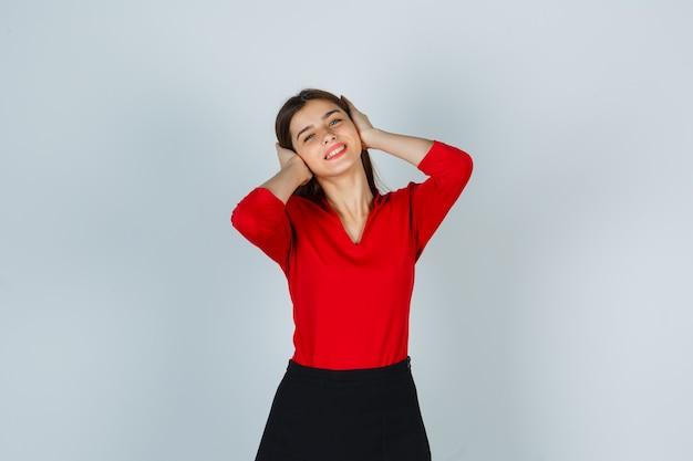 Jovem de mãos dadas nas orelhas com blusa vermelha, saia e parecendo feliz