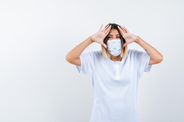 Jovem de mãos dadas nas têmporas para ver claramente em t-shirt branca e máscara e olhando com foco, vista frontal.
