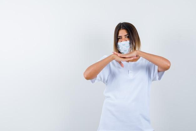 Jovem de mãos dadas sob o queixo em uma máscara e camiseta branca e parece confiante. vista frontal.