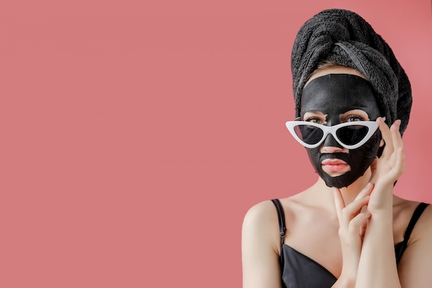 Jovem de óculos appling máscara facial de tecido cosmético preto. máscara de peeling facial com carvão, tratamento de beleza spa, cuidados com a pele, cosmetologia. fechar-se