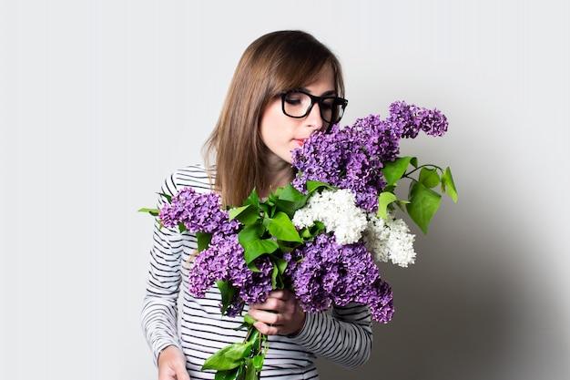 Jovem de óculos aprecia o aroma de um buquê de lilases sobre um fundo claro.