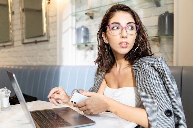 Jovem de óculos com laptop em um café. morena sorridente trabalhando remotamente.