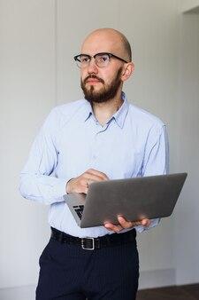 Jovem de óculos com um laptop em uma sala iluminada