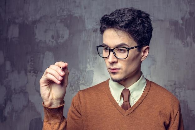 Jovem de óculos, como se estivesse tocando uma placa visual