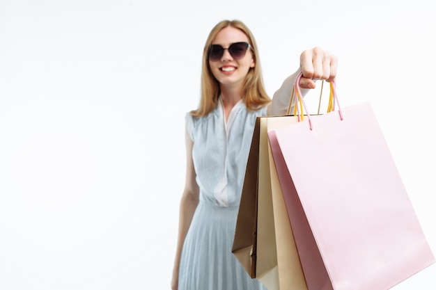 Jovem de óculos compras, posando com sacolas de presente