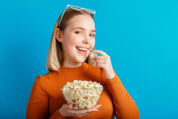 Jovem de óculos de cinema. o espectador de um filme adolescente come pipoca isolada sobre um fundo de cor azul