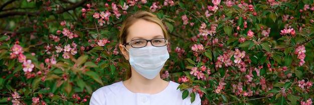 Jovem de óculos e máscara médica por uma árvore florida. retrato de uma linda médica bem preparada no parque verde de verão.