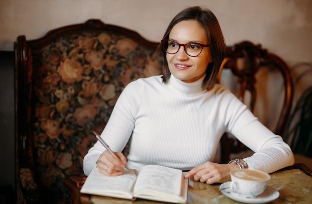 Jovem de óculos escreve para fazer uma lista de metas, escrevendo em um diário em um café. sorri e desvia o olhar