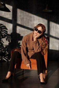 Jovem de óculos escuros da moda e casaco em uma poltrona no interior. menina modelo com roupa de primavera, posando no interior. estilo de vida da cidade. moda feminina. retrato do close up.