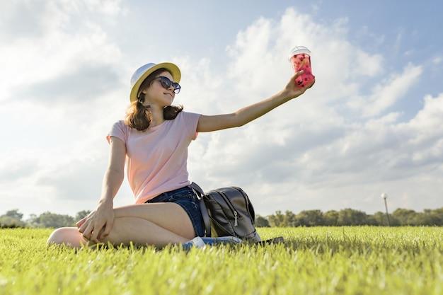 Jovem de óculos escuros e chapéu bebe bebida de frutas de verão