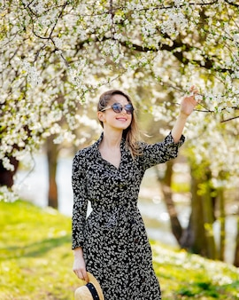 Jovem de óculos escuros e chapéu fica perto de uma árvore florida no parque. temporada de primavera