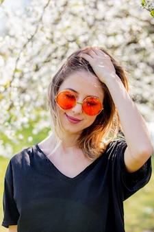 Jovem de óculos escuros fica perto de uma árvore florida no parque. temporada de primavera