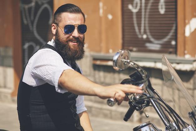 Jovem de óculos escuros sentado em uma motocicleta