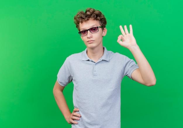 Jovem de óculos escuros vestindo camisa pólo cinza feliz e positivo mostrando sinal de ok em pé sobre a parede verde
