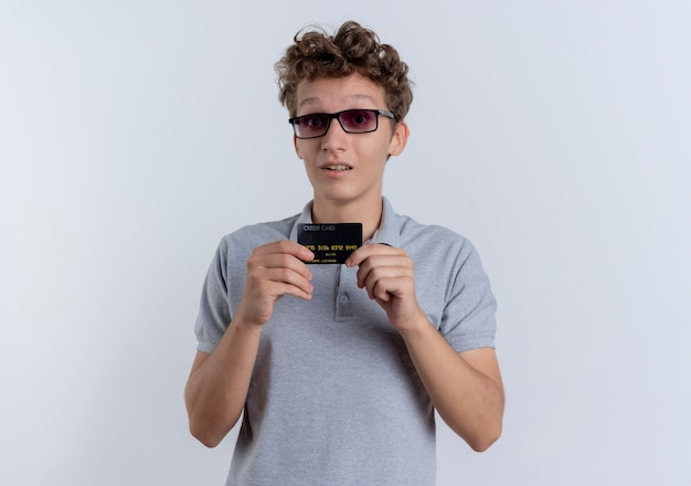 Jovem de óculos escuros vestindo uma camisa pólo cinza mostrando um cartão de crédito surpreso em pé sobre uma parede branca