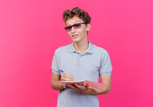 Jovem de óculos escuros vestindo uma camisa pólo cinza segurando um caderno com uma caneta feliz e positivo sorrindo em pé sobre a parede rosa