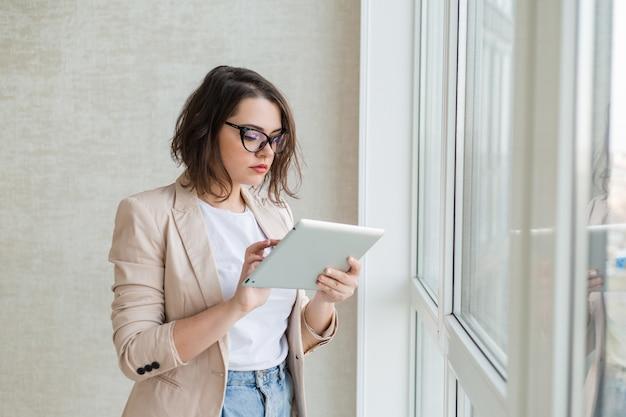Jovem de óculos para visão fica ao lado da janela da casa segurando um tablet