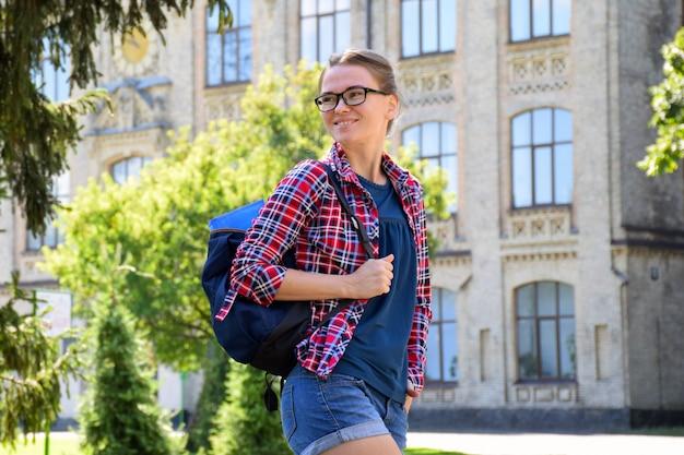 Jovem de óculos parada ao ar livre perto da universidade