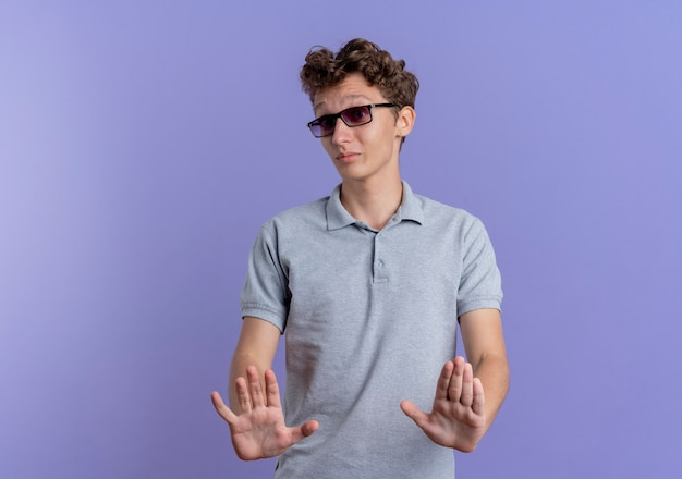 Jovem de óculos pretos, vestindo uma camisa pólo cinza fazendo sinal de pare de mãos dadas, dizendo para não se aproximar em pé sobre a parede azul