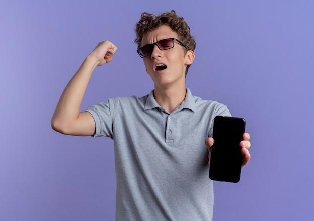 Jovem de óculos pretos, vestindo uma camisa pólo cinza, mostrando o smartphone cerrando o punho feliz e animado em pé sobre a parede azul