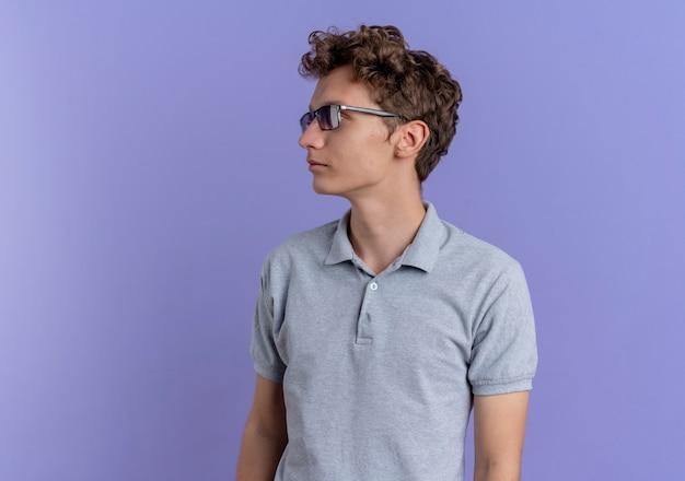 Jovem de óculos pretos vestindo uma camisa pólo cinza olhando para o lado com uma cara séria em pé sobre a parede azul
