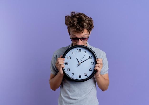 Jovem de óculos pretos vestindo uma camisa pólo cinza segurando um relógio de parede, parecendo preocupado em pé sobre a parede azul