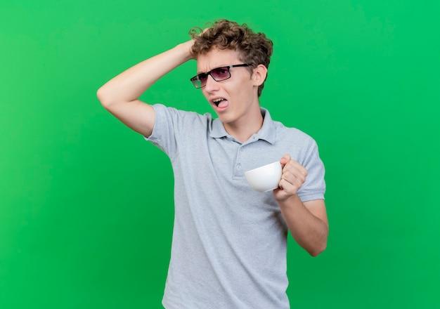 Jovem de óculos pretos, vestindo uma camisa pólo cinza, segurando uma xícara de café, parecendo confuso com a mão na cabeça por engano em pé sobre uma parede verde