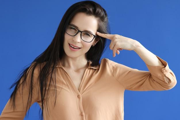 Jovem de óculos segurando o dedo indicador perto da testa sobre fundo azul