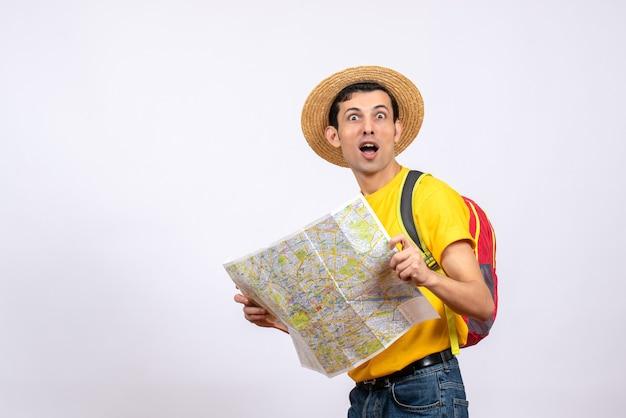 Jovem de olhos arregalados de frente com chapéu de palha e camiseta amarela