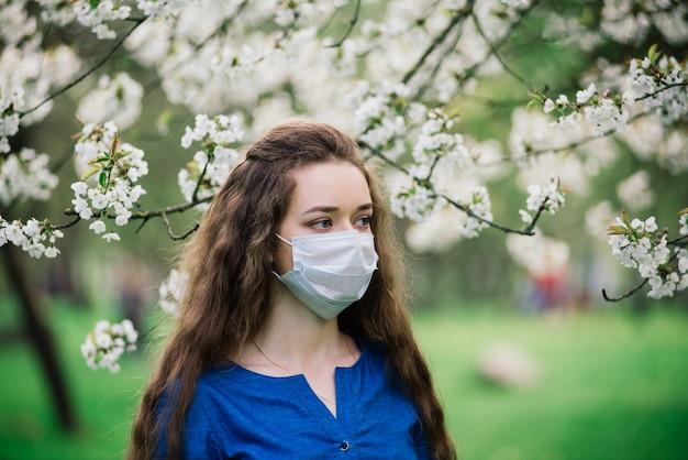 Jovem de olhos azuis usando máscara em um parque florido