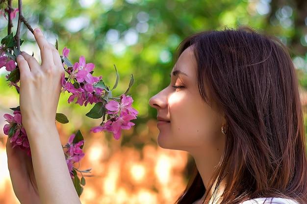Jovem de olhos fechados cheira flores cor de rosa no galho de macieira.