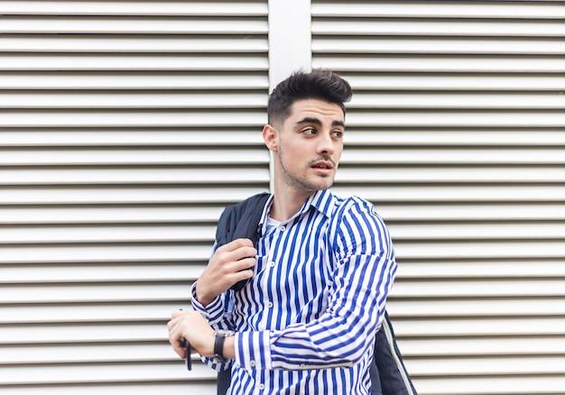 Jovem de pé ao ar livre enquanto olha o relógio de pulso e fala por telefone