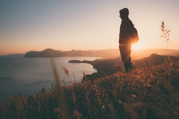Jovem de pé com mochila. alpinista na pedra à beira-mar no céu colorido do sol. bela paisagem com homem desportivo rochas mar e nuvens ao pôr do sol. estilo de vida esportivo