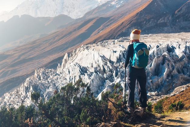 Jovem de pé com mochila no pico da montanha e olhando belas montanhas e geleiras ao pôr do sol