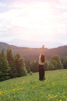 Jovem de pé com um buquê de flores e mãos levantadas