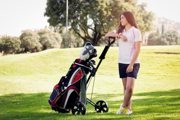 Jovem de pé com um saco de tacos de golfe