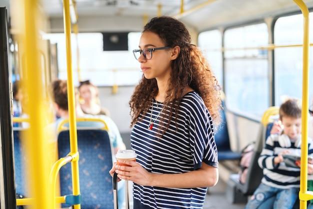 Jovem de pé e andando no transporte público e olhando pela janela.