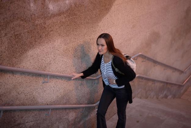 Jovem de pé e as escadas da passagem subterrânea, segurando o estômago