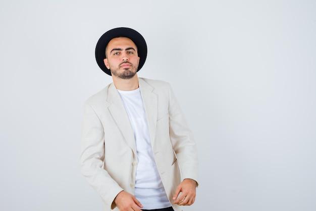Jovem de pé em linha reta e posando de camiseta branca, jaqueta e chapéu preto e olhando sério. vista frontal.