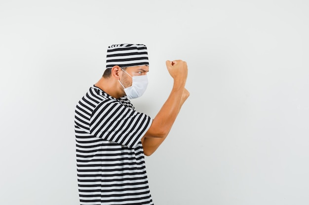 Jovem de pé em pose de boxeador em camiseta listrada, chapéu, máscara e parecendo decidido.