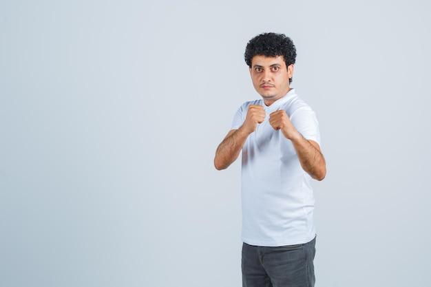 Jovem de pé em pose de boxeador em jeans e camiseta branca e olhando sério. vista frontal.