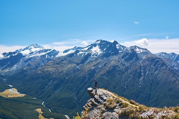 Jovem de pé em um penhasco olhando para o vale na nova zelândia